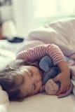 睡觉与她的被充塞的玩具的逗人喜爱的小女孩 免版税库存图片