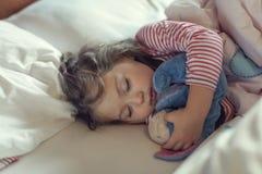 睡觉与她的被充塞的玩具的逗人喜爱的小女孩 库存图片
