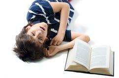 睡觉与开放书的年轻学生在他旁边 库存图片