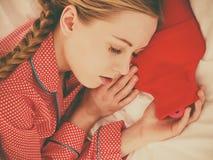 睡觉与温暖的炽热水瓶的妇女 免版税库存照片