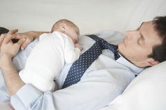 睡觉与父亲的新出生的婴孩在床上 库存图片