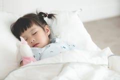睡觉与玩偶的逗人喜爱的矮小的亚裔女孩在床上 免版税库存图片