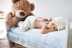 睡觉与玩具熊的小婴孩 免版税库存照片