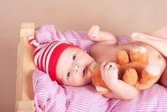 睡觉与玩具熊的逗人喜爱的男婴在床上 库存照片