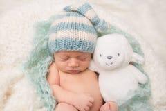 睡觉与玩具的新出生的婴孩 免版税库存照片