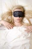 睡觉与眼罩的美丽的少妇 免版税库存照片