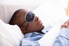 睡觉与睡眠面具的人 库存图片