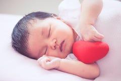 睡觉与红色心脏的逗人喜爱的亚裔新出生的女婴 免版税图库摄影