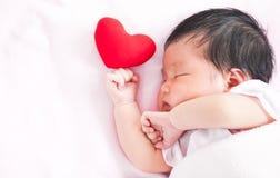 睡觉与红色心脏的逗人喜爱的亚裔新出生的女婴 库存图片