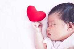 睡觉与红色心脏的逗人喜爱的亚裔新出生的女婴 免版税库存照片