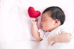 睡觉与红色心脏的逗人喜爱的亚裔新出生的女婴 免版税库存图片