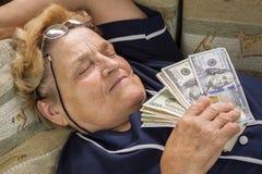 睡觉与金钱的妇女领抚恤金者在她的手上 免版税库存图片