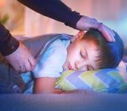 睡觉和作梦在他的床上的小男孩 免版税库存照片