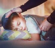 睡觉和作梦在他的床上的小男孩 免版税图库摄影