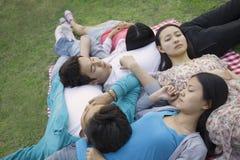 睡觉和基于彼此的五个朋友在一顿野餐期间在公园 免版税库存图片