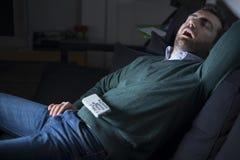 睡觉和打鼾在电视前面的人 免版税库存图片