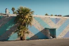 睡觉在一个五颜六色的大厦后的无家可归者 免版税库存图片
