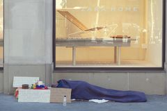 睡觉在一个扎拉家商店窗口前面的街道的无家可归者在Paseig de加西亚 库存照片