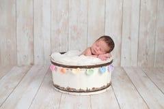 睡觉在一个木桶的新出生的女婴 免版税库存图片