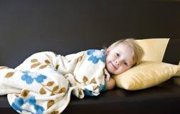 睡觉在一个棕色沙发的女孩 免版税图库摄影