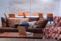 睡觉在一个沙发的妇女在一个创造性的办公室 免版税图库摄影