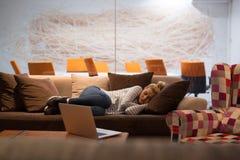 睡觉在一个沙发的妇女在一个创造性的办公室 免版税库存图片
