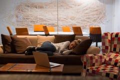 睡觉在一个沙发的妇女在一个创造性的办公室 库存图片