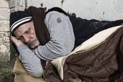 睡觉在一个老睡袋的无家可归的人 免版税库存图片