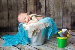 睡觉在一个银色金属桶的新出生的男婴 库存图片