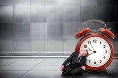 睡觉在一块巨型手表附近的人 免版税库存照片