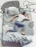 睡觉在一张大白色床和他的梦想上的年轻人顶视图照片 库存照片