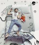 睡觉在一张大白色床和他的梦想上的年轻人顶视图照片 免版税库存照片