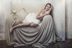 睡觉在一把巨大的舒适的椅子的美丽的年轻亭亭玉立的妇女 免版税库存照片
