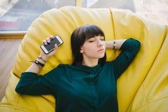 睡觉在一把舒适的椅子的断裂和拿着电话的年轻美丽的妇女 一个现代办公室的画象 免版税库存图片