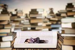 睡觉在一本开放书的小少妇 免版税库存图片