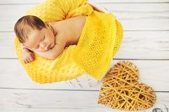 睡觉在一条黄色毯子的逗人喜爱的婴孩 库存照片