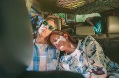 睡觉在一辆后座汽车的疲乏的妇女朋友 免版税库存照片