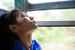 睡觉在一辆移动的公共汽车上的妇女 免版税库存图片