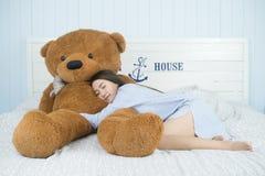睡觉在与一个大棕色玩具熊的床上的亚裔女孩 免版税库存图片