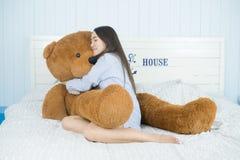 睡觉在与一个大棕色玩具熊的床上的亚裔女孩 库存图片