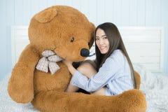 睡觉在与一个大棕色玩具熊的床上的亚裔女孩 库存照片