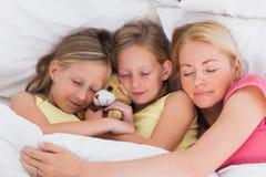 睡觉在与她逗人喜爱的孩子的床上的妇女 免版税库存照片