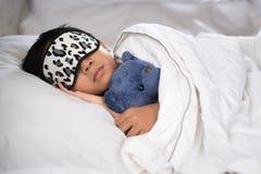 睡觉在与戴着睡眠面具的玩具熊白色枕头和板料的床上的男孩 免版税库存照片