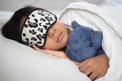 睡觉在与戴着睡眠面具的玩具熊白色枕头和板料的床上的男孩 库存照片