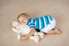 睡觉在与玩具和牛奶瓶的地板上的婴孩 免版税库存图片