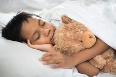 睡觉在与玩具熊白色枕头和板料的床上的男孩 免版税图库摄影
