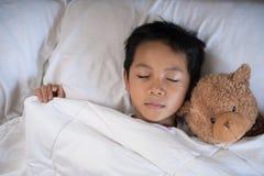 睡觉在与玩具熊白色枕头和板料的床上的男孩 库存图片