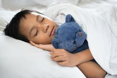 睡觉在与玩具熊白色枕头和板料的床上的男孩 库存照片