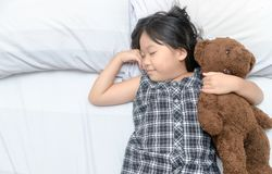 睡觉在与玩具熊的床上的逗人喜爱的女孩 图库摄影