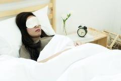 睡觉在与眼罩的床上的俏丽的妇女 库存图片